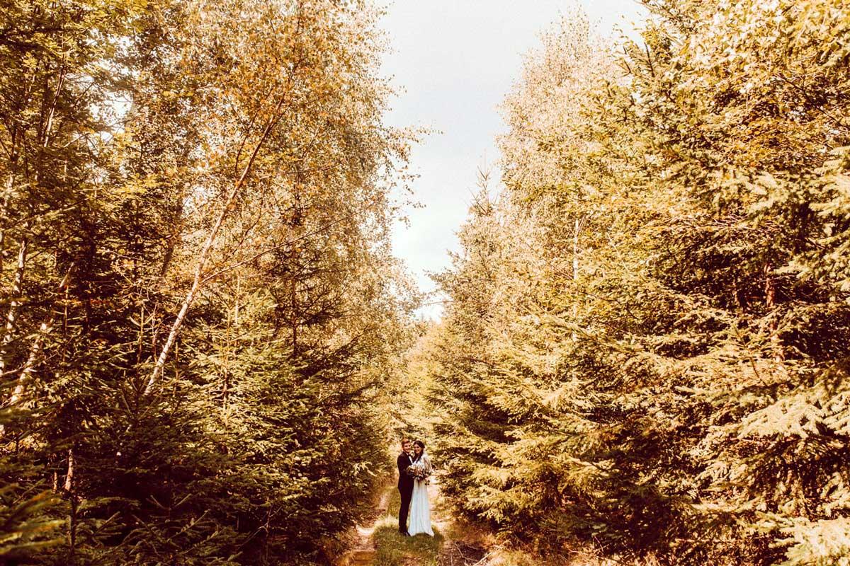 Para Młoda spaceruje w środku lasu w promieniach słońca oczami fotografa ślubnego z Tarnowa Emilii Chrobok