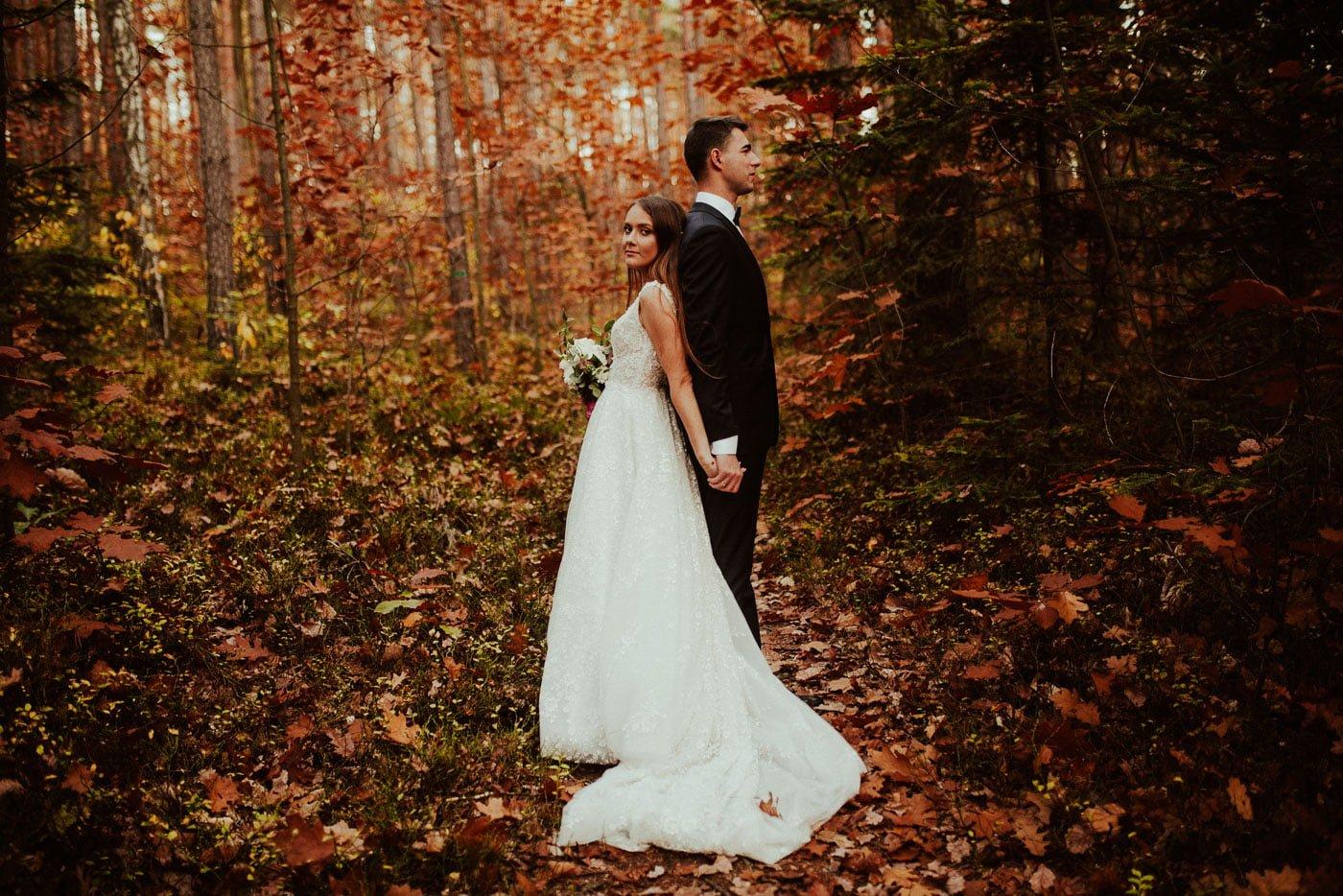 Para Młoda w środku jesienneo lasu uchwycona w kadrze Emilii Chrobok fotografa działającego w Tarnowie