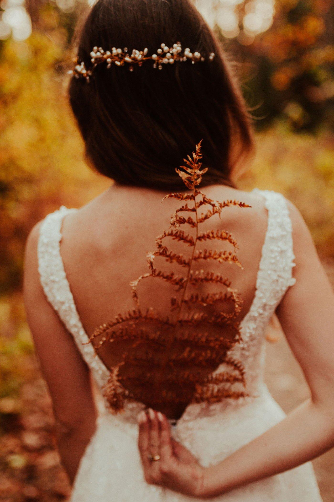 Panna Młoda trzymająca jesienną roślinę w kadrze wykonanym przez Emilię Chrobok - fotografa ślubnego z Tarnowa